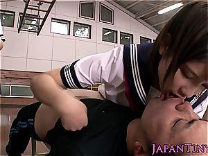 mischievous young japanese schoolgirls sharing wood