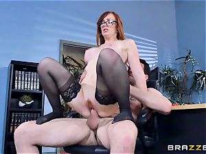Dani Jensen toying with spear in the office